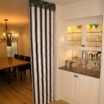 simple room divider idea design in dining room madeof stripe patterned black and white curtain and wooden floor and small cabinet