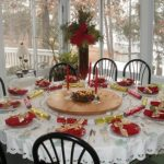 simple white and red christmas decoration idea with round table with lace table cloth and black chairs and centerpiece and acrylic candle holder