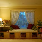 simple white bay window couch design with sheer white curtain and red cushion design with storage and bookshelves and creamy area rug