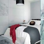 simple white bedroom design wih gray sheet and red blanket and white panel siding and concrete flooring and black drum lamp shade