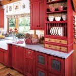 small L shaped red country kitchen design with white top and glass window and french curtain and wooden floor and patterned runner rug