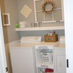 small basement laundry room idea with white cabinetry and wall rack and wreath and storage bins and brown patterned area rug