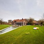 small farm house design with long narrow pool in the middle of greenery with grassy meadow and open plan