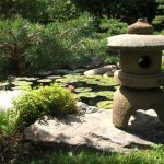 small japanese garden design idea with stone patioand shrub and greenery and mini temple for lantern and grass