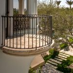 small round stone balcony design idea with iron femce and stone flooringa dn white siding and glass window and garden view