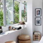 small white sunroom design idea with glass window and concrete desk beneath the window and pouff and stools and patterned area rug and wall pictures