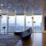 spacious interior of apartment with city view with wooden flooring patterned area rug and modern futuristic couch and glass floor to ceiling window and mirrored ceiling