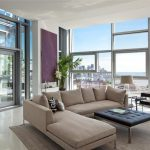 Stunning Apartment Design With City View From Open Plan With Glass Enclosure And Creamy Sofa And Black Tufted Coffee Table And Indoor Plant And Purple Accen