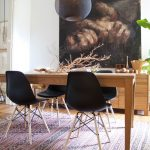 stunning black vintage chairs design and wooden table and patterned ethnic area rug and black spooky painting on the wall