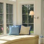 stunning creamy bay window couch design with blue cushions and rattan basket and arched baord and wall lamp