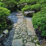 stunning green small japanese garden idea with stone walkway with shrub and boulders and pebbles