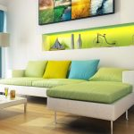 stunning modern living room design with green couch and yellow and blue cushion and green lighting accent on the wall rack