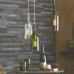 stunning wine bottle chandelier with single wire suspension above round small dining table with rattan chairs with stone wall accent and floating rustic vanity