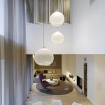 stylish and minimalist white living room design with white siding and balls pendants and round dining rabke and comfortable creamy sofa idea