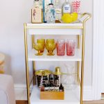 stylish bar cart accessories in metal cart with wheels plus liquors and wine plus lime and small metal ice bucket and shakers