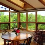 sunroom design with full of sereinity and open plan and wooden ceiling and siding and skylight and breakfast nook with wooden table and chair and wooden flooring