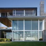 super classy modern eco friendly house deisgn with full glass siding idea with three storey model and green grassy meadow