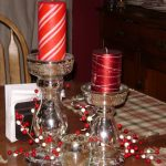 two simple and elegant acrylic candle holder for red candles on table with red and white tiny balls decoration