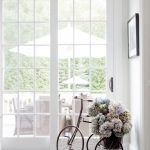 unique bicycle shaped wrought iron flower stand idea in white room design with glass window and wall palette