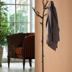 unique black tree shaped coat rack ideas in a room with peach paint wall and marroon chair aside glass window design