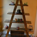 unique brown furnished modern ladder bookshelf idea with storage bin beneath orange painted wall and wooden floor