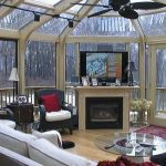 unique sunroom design idea with fireplace and tvset and white sectional seating and black red area rug and glass round coffee table and cone ceiling design