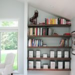unqiue space saver creative shelving idea in the loft with sloping design on wooden floor aside glass window with white couch