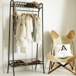 vintage black iron coat rack ideas with shoes storage and clothes hanger and comfortable chair with white cushion and brown rug