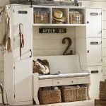 vintage white hall storage idea with upper racks and storage bins with rattan basket and closet and hooks and wooden wall and bench