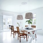 vintage white interior design for dining space with unique drum lamp shade and white dining table and wooden chairs and indoor plants