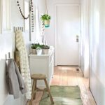 vintage white narrow corridor design idea with white console table and wooden bench and green runner rug and coat hools and wall string lamps and indoor plats