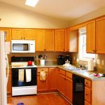warm kitchen makeovers on a budget with brown kitchen cabinets and wooden laminate flooring and modern stove and oven plus refrigerator