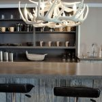 white antler chandelier in rustic kitchen ideas decorated above kitchen counter with granite countertop plus black leather kitchen bar stool with interesting wall shelvess