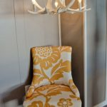 white antler chandelier in the corner of the room with super comfy chair with yellow white chair for reading plus rug