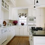 white kitchen makeovers on a budget with white cabinets and white and black granite countertop plus cute window valance plus admirable laminate flooring and pendant lamp