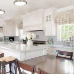 wonderful large kitchen design with seating and dining set and white cabinetry and glass window and cool ceiling light