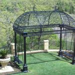 wrought iron pergola in black materials with amazing decorative roof and swings in the each side plus white potted plants and balcony