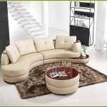 Apartment sized sectional idea in cream dark shaggy area rug round wood top center table
