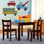 Dark finished wood table with a couple of dark finished wood chairs for children car themed wall art area rug