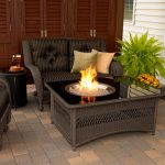 Fire pit table with black glass top for indoor dark rattan chairs with black and strip patterned cushions