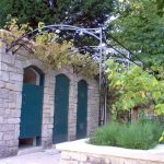 Grapevine Wrought Iron Pergola On Stone Wall