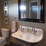 Kohler trough sink idea in white with two units of water faucet black framed mirror a rattan storage box