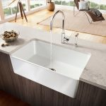 Large and deep white farm sink with simple water faucet in a kitchen island