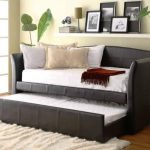 Large sized daybed frame with trundle addition and mattress plus pillows white shaggy rug floating white shelf for picture frame books and some decorative items