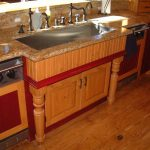 Larger and deeper farm sink and double faucets  brown granite kitchen countertop wooden base cabinet under sink