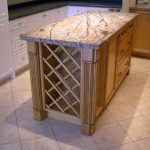 Light brown kitchen island with light brown countertop drawer system and simple wine storage