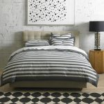 Mide century modern bedding idea in monochromatic stripped pattern monochromatic bedroom rug idea cool wooden bedside table with modern table lamp