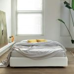Modern bed without headboard idea with white bedding and yellow accent pillows