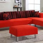 Modern minimalist red sectional with metal legs and black back cushions two throw pillows