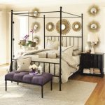 Purple upholstered end bed bench with black wrought iron legs black wrought iron bed frame with iron headboard and pillars black painted wood bedside table several decorative round mirrors